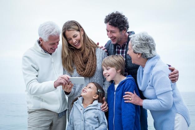 Glückliche familie, die im telefon schaut