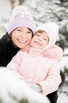 Glückliche familie, die im winter draußen spielt