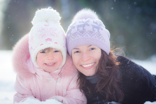 Glückliche familie, die im winterpark auf schnee liegt