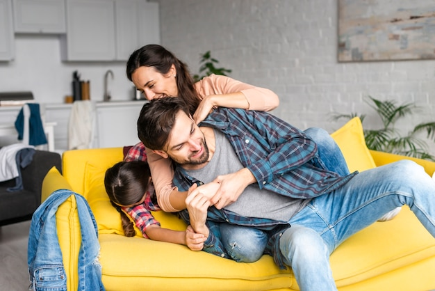 Glückliche familie, die im wohnzimmer herumalbert