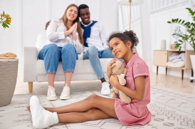 Glückliche familie, die im wohnzimmer stillsteht. mutter, vater und ihre tochter posieren zu hause zusammen, gute beziehung. mama, papa und weibliches kind
