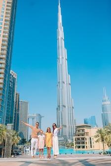 Glückliche familie, die in dubai mit burj khalifa wolkenkratzer im hintergrund geht.