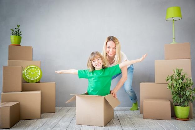 Glückliche familie, die in ein neues zuhause spielt mutter und kind, die zusammen spaß haben umzugstag