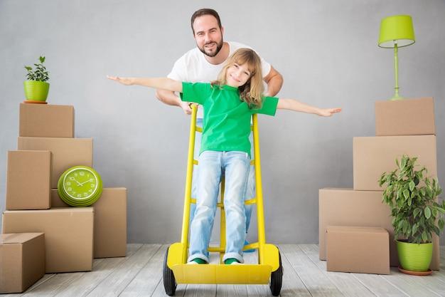 Glückliche familie, die in ein neues zuhause spielt, vater und kind, die spaß am umzugstag haben