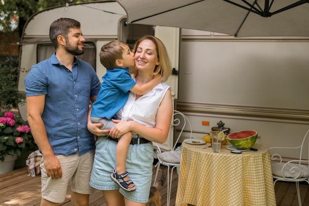 Glückliche familie, die in einem wohnwagen mit kopienraum lebt