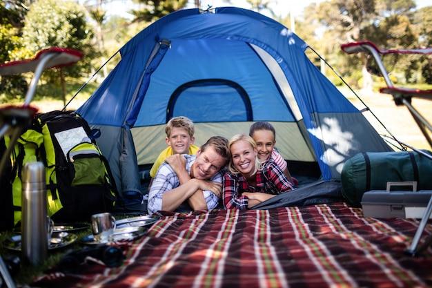 Glückliche familie, die in einem zelt liegt