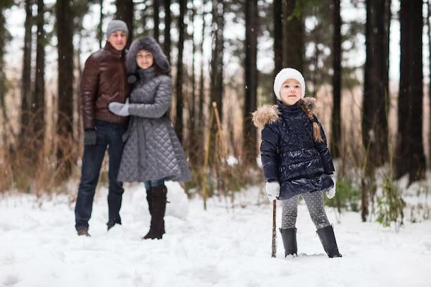 Glückliche familie, die in einen winterpark geht.
