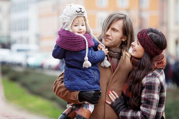 Glückliche familie, die in herbststadt geht und spaß hat