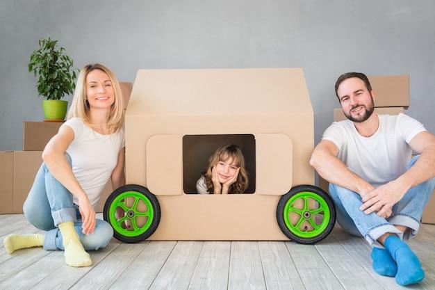 Glückliche familie, die in neues zuhause spielt, vater, mutter und kind, die spaß am umzugstag haben