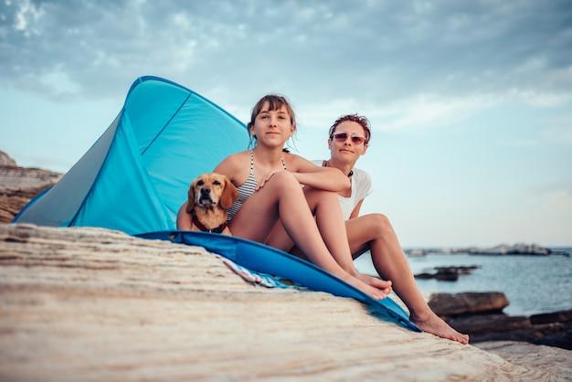 Glückliche familie, die innerhalb des strandzeltes mit hund durch das meer sitzt