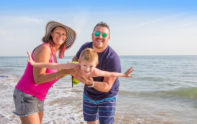 Glückliche familie, die jungenhände am strand hält