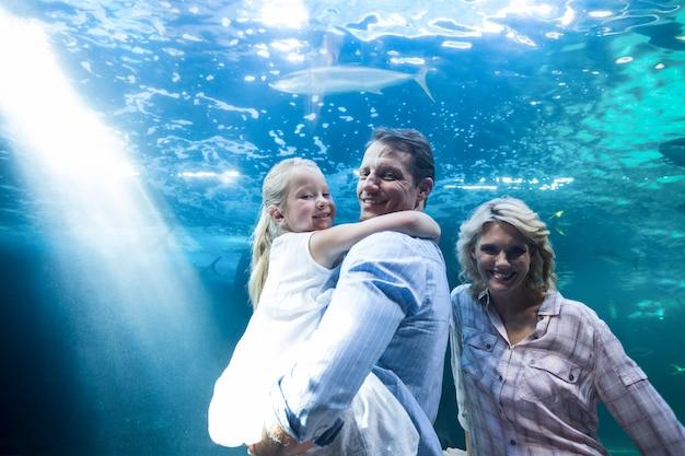 Glückliche familie, die kamera hinter einem aquarium betrachtet