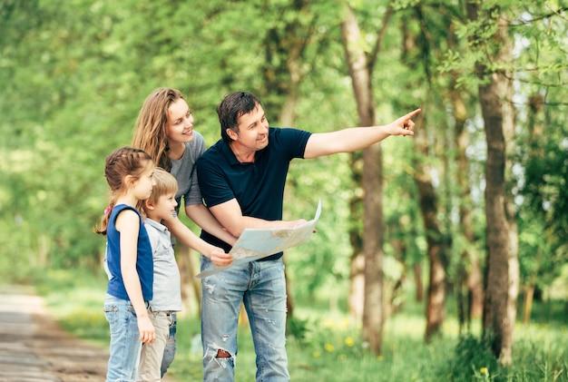 Glückliche familie, die karten während der reise im park betrachtet