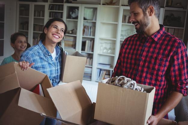 Glückliche familie, die kartonboxen zusammen auspackt