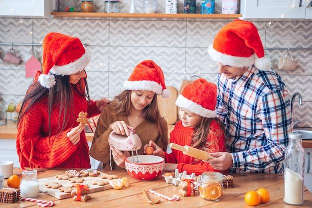 Glückliche familie, die kekse für weihnachten in der küche vorbereitet