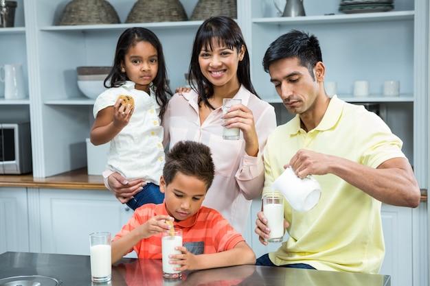 Glückliche familie, die kekse isst und milch trinkt