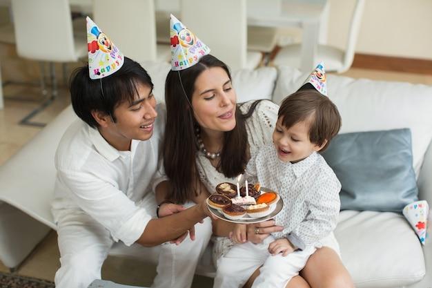 Glückliche familie, die kerzen für einen geburtstag zu hause zusammenbläst
