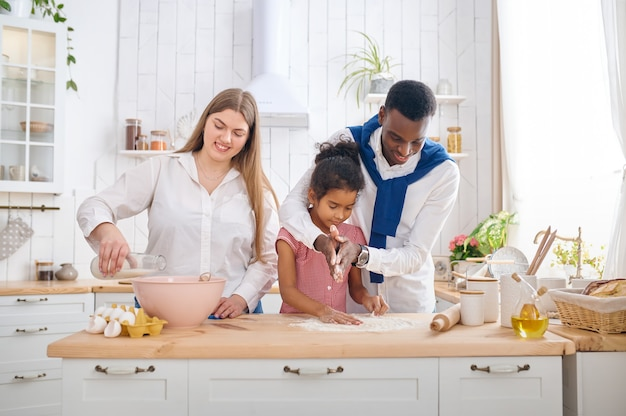 Glückliche familie, die kuchen zum frühstück in der küche kocht. mutter, vater und ihre tochter bereiten morgens den teig vor, gute beziehung