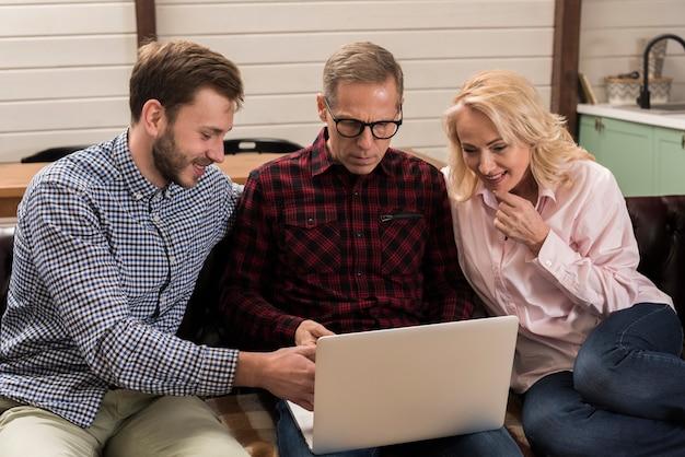 Glückliche familie, die laptop auf sofa betrachtet