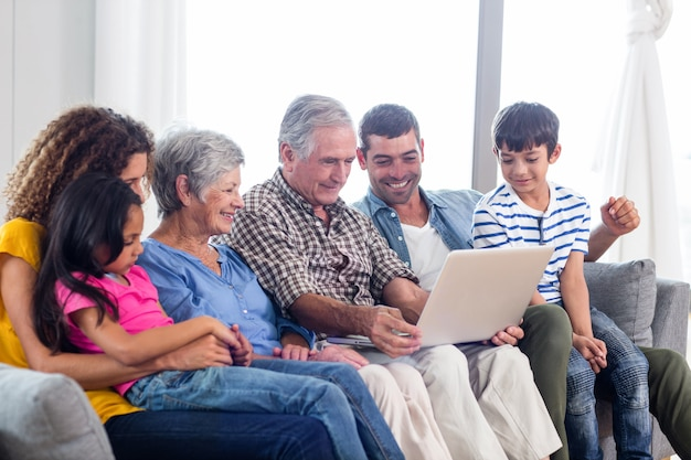 Glückliche familie, die laptop auf sofa verwendet