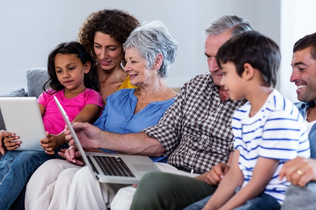 Glückliche familie, die laptop und digitale tablette im wohnzimmer verwendet