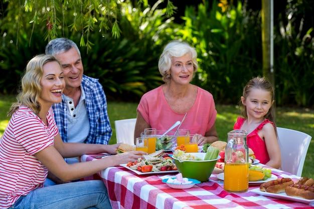 Glückliche familie, die mahlzeit im yard hat