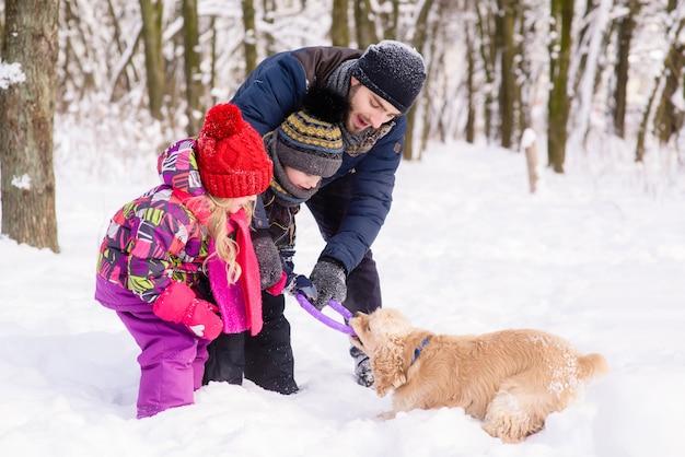 Glückliche familie, die mit einem hund im schnee draußen spielt