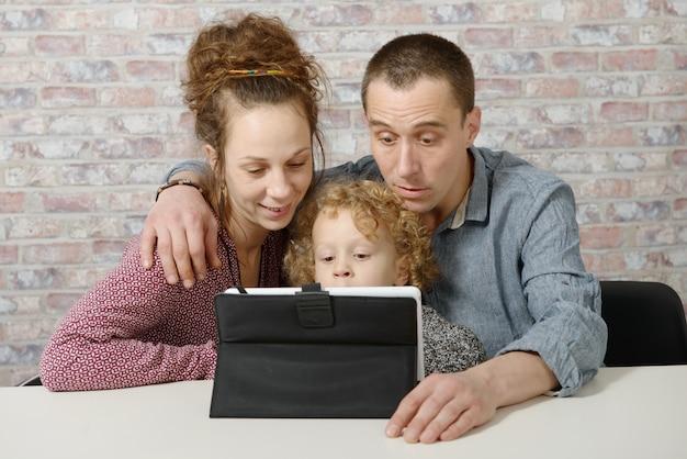 Glückliche familie, die mit einem tablet-computer spielt