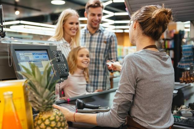 Glückliche familie, die mit einer kreditkarte zahlt