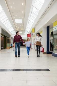 Glückliche familie, die mit einkaufstaschen geht