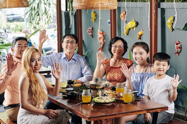 Glückliche familie, die mit händen winkt