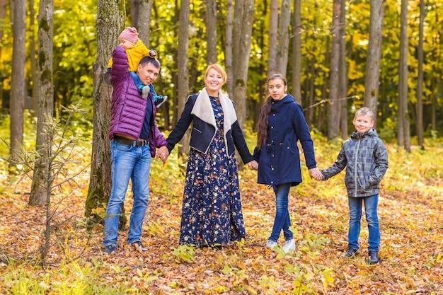 Glückliche familie, die mit herbstlaub im park spielt
