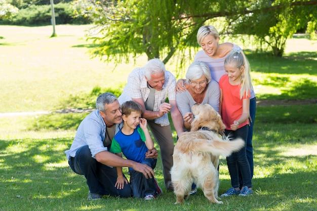 Glückliche familie, die mit ihrem hund spielt