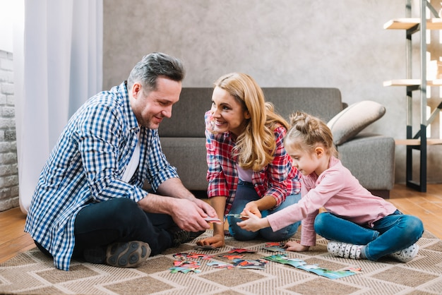 Glückliche familie, die mit puzzlespielstücken mit tochter spielt