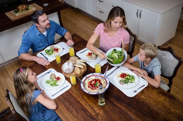 Glückliche familie, die miteinander beim essen in der küche spricht