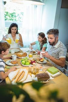 Glückliche familie, die miteinander spricht, während sie zusammen frühstücken