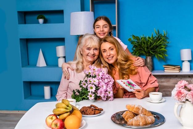 Glückliche familie, die morgens zu hause frühstückt und geburtstag feiert
