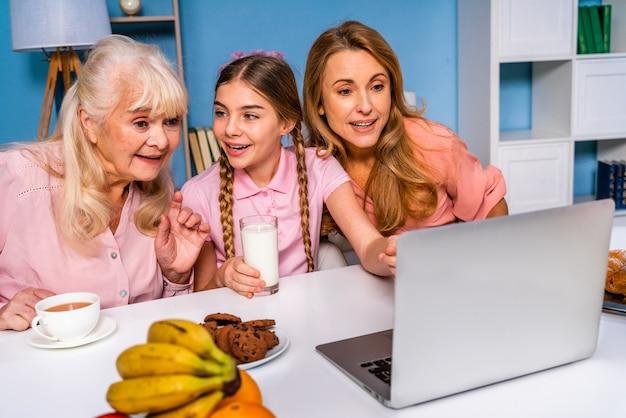 Glückliche familie, die morgens zu hause frühstückt, während sie einen videoanruf hat