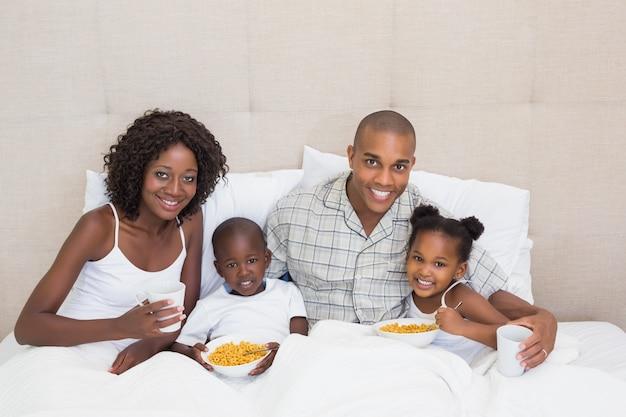 Glückliche familie, die morgens zusammen im bett frühstückt