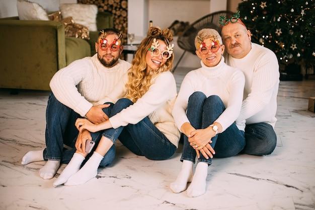 Glückliche familie, die partybrille trägt und auf dem boden neben schön geschmücktem weihnachtsbaum sitzt