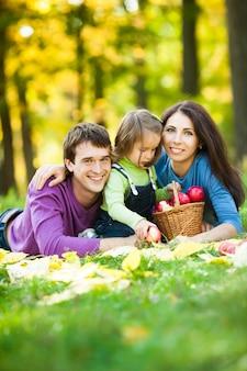 Glückliche familie, die picknick gegen unscharfen herbstlaubhintergrund hat