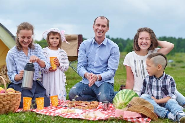Glückliche familie, die picknick in wiese an einem sonnigen tag hat. familie genießt campingurlaub auf dem land