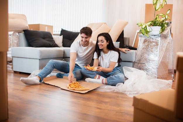 Glückliche familie, die pizza am umzugstag isst. bild eines jungen paares, das ruhezeit beim zusammensitzen im neuen haus genießt.