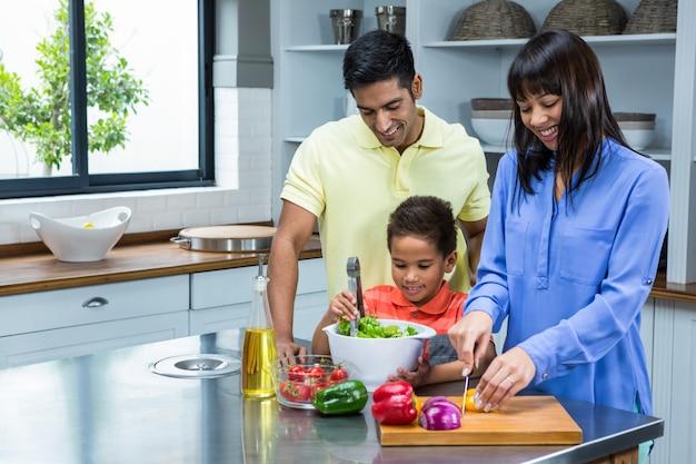 Glückliche familie, die salat in der küche zubereitet