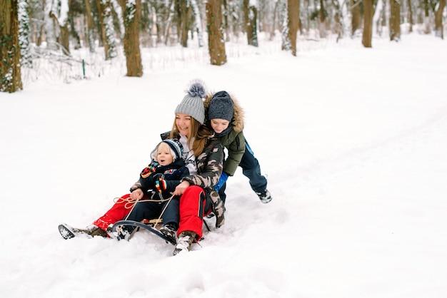 Glückliche familie, die schlitten auf dem schnee fährt