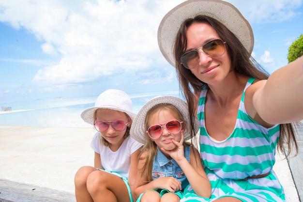 Glückliche familie, die selfie am tropischen strand nimmt