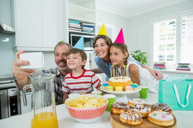 Glückliche familie, die selfie auf handy in der küche nimmt