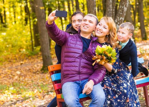 Glückliche familie, die selfie durch smartphone im herbstlichen park nimmt