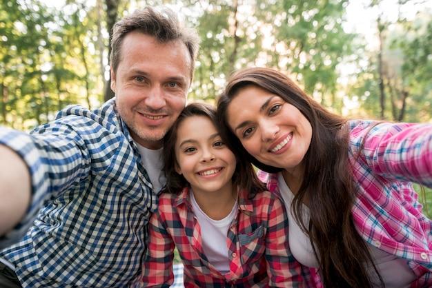Glückliche familie, die selfie im park nimmt