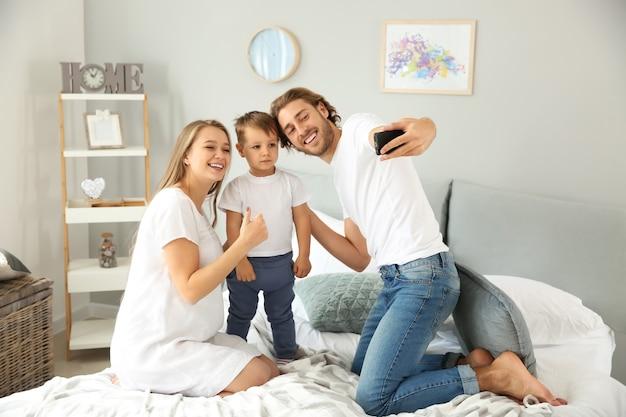 Glückliche familie, die selfie im schlafzimmer macht